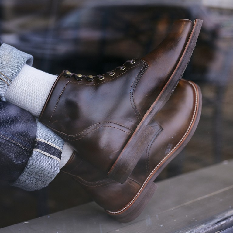 Men's casual boots shown through a window